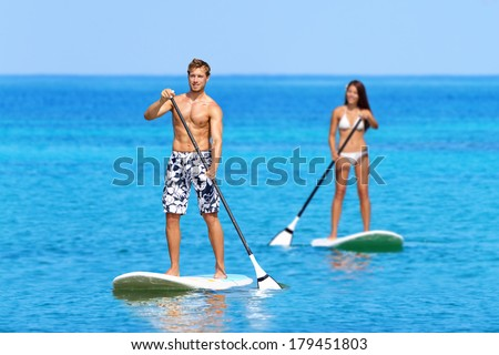 Paddleboard beach people on stand up paddle board surfboard surfing in ocean sea on Big Island, Hawaii Beautiful young multi-ethnic couple, mixed race Asian woman and Caucasian man doing water sport. - stock photo