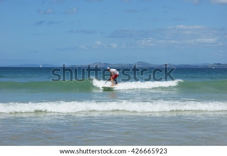Paddleboarder on a SUP surfing a wave. Paddle boarder photographed in Northland, New Zealand. - stock photo
