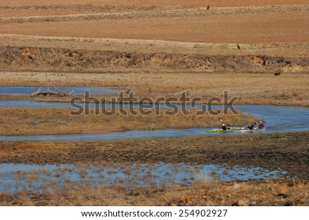 Paddlers follow the meandering contours of a river in their canoes. - stock photo