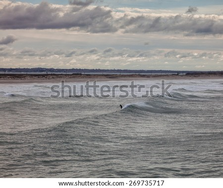 Paddlesurfer catching a wave.  Taken at Second Beach in Middletown RI. - stock photo