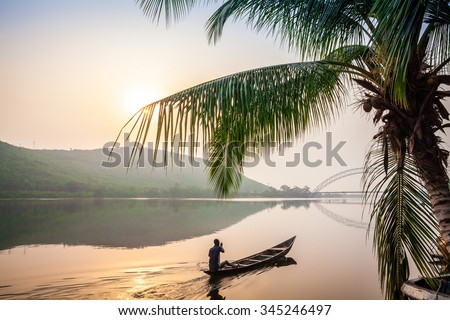 Paddling in traditional wooden canoe, Ghana, Africa - stock photo