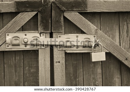 Padlock and a locking bar on an old wooden door (in sepia, vintage style) - stock photo