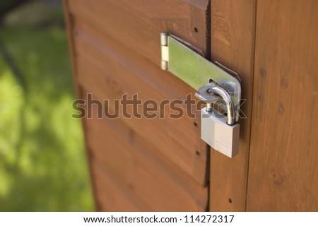 Padlock on wooden shed door - stock photo