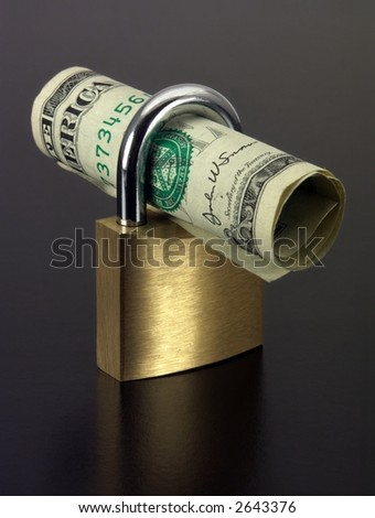 Padlock with a dollar rolled up inside. - stock photo