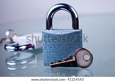 Padlock with a key on a glass table - stock photo