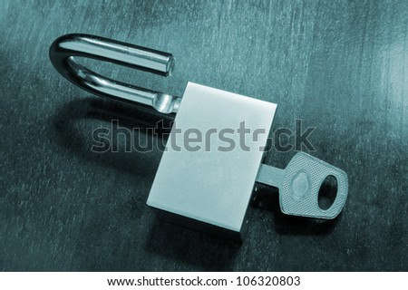 Padlock with key on wooden table - stock photo