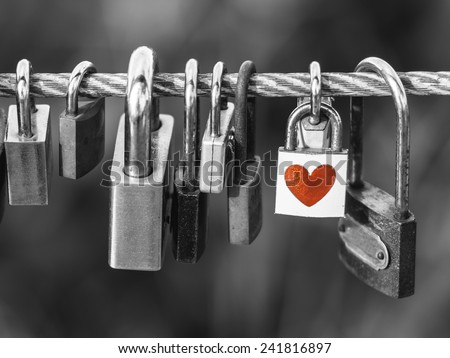 Padlocks with heart shape on rope bridge over black and white background - stock photo