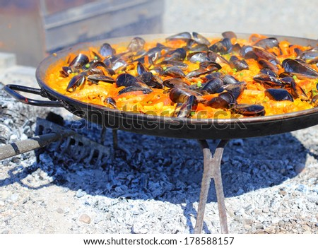 paella cooking over hot coals - stock photo