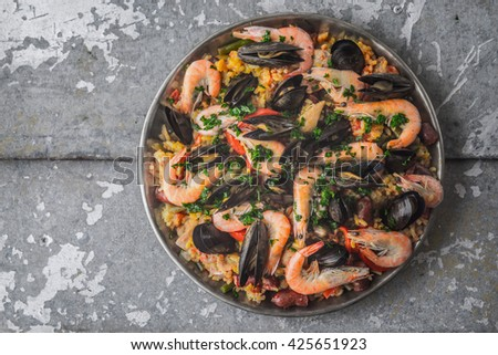Paella in the metal plate on the metal background top view - stock photo