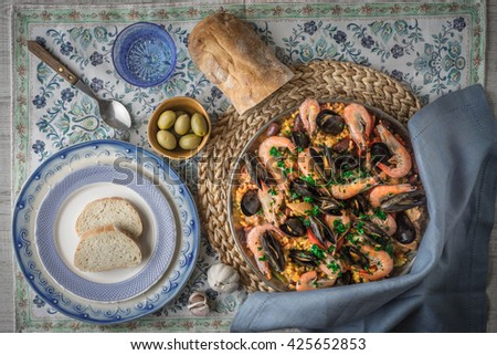 Paella on the metal plate on the beautiful napkin with tableware and bread top view - stock photo