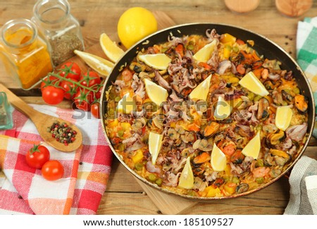 Paella with seafood on wooden table - stock photo