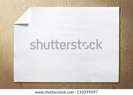 page of White paper folded on wood background with shadow - stock photo