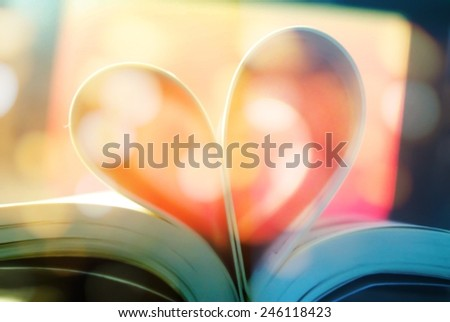 pages of a book curved into a heart shape with bokeh - stock photo