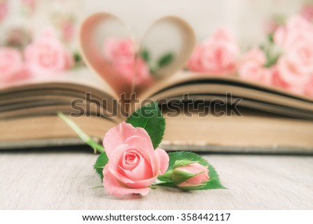 Pages of an old book curved into a heart shape and little pink roses on wooden table. Valentine's day card. - stock photo