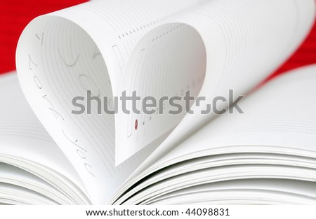 pages of book curved into a heart shape - stock photo