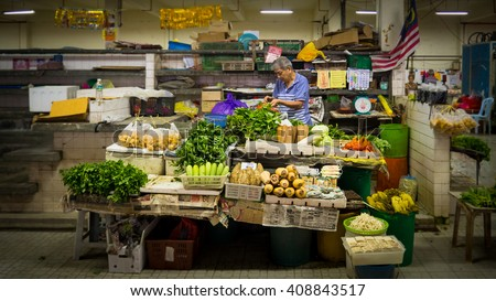 PAHANG, MALAYSIA - APRIL 21, 2016: Chinese man sells vegetables and fruits in Pasar Besar Bentong, a small town in the west side of Pahang Darul Makmur, Malaysia. - stock photo