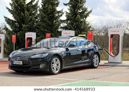 PAIMIO, FINLAND - APRIL 29, 2016: Black Tesla Model S electric car which operates as taxi cab is being charged at Tesla Supercharger Station of Paimio.  - stock photo