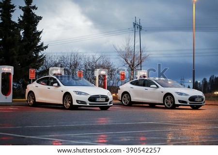 PAIMIO, FINLAND - NOVEMBER 14, 2015: Two Tesla Model S cars are charged at Tesla Supercharger station at night. Tesla Supercharging stations charge up to 16 times as fast as public charging stations. - stock photo