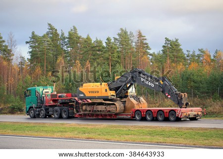 PAIMIO, FINLAND - OCTOBER 23, 2015: Volvo FH truck hauls Volvo EC460 BLC hydraulic crawler excavator. The excavator weighs 46 tonnes.  - stock photo