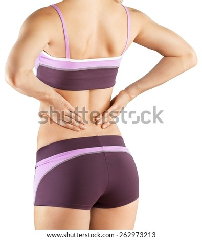 Pain. Back pain. Athletic woman in pink sportswear standing at the seaside rubbing the muscles of her lower back, cropped torso portrait. - stock photo