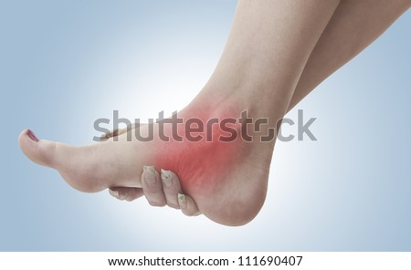 Pain in a woman ankle. Female holding hand to spot of ankle-ache. Concept photo with Color Enhanced skin with read spot indicating location of the pain. - stock photo