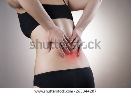 Pain in back of women on gray background. Caring for the female body. Red dot - stock photo