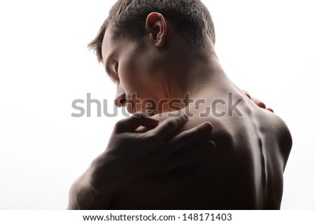 Pain in shoulders. Rear view of young shirtless men touching his shoulders by the hands and keeping eyes closed while standing isolated on grey - stock photo