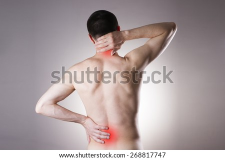 Pain in the back and neck in men on gray background. Red dot - stock photo