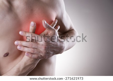 Pain in the heart of a man on gray background. - stock photo