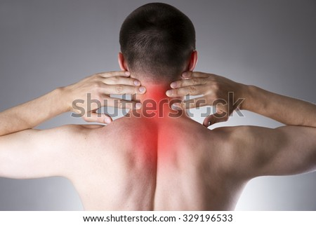 Pain in the neck. Man with backache. Pain in the man's body on a gray background with red dot - stock photo