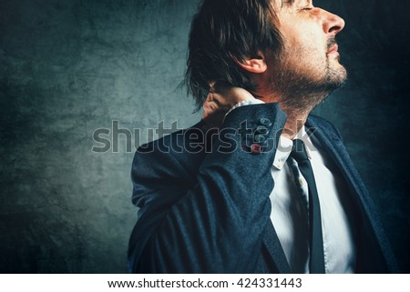 Pain in the neck of a businessman, stressed person in elegant suit with painful face expression - stock photo