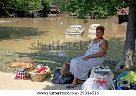PAINESVILLE, OHIO - JULY 16: An unitentified woman sits with her only remaining items saved from her home.  July 16th 2006 in Painesville, Ohio. - stock photo