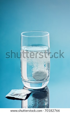 Painkiller tablet in glass of water with bubbles over blue background. Vertical. copy-space. - stock photo