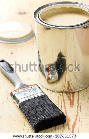 paint brush and tin can on crackle wooden background - stock photo
