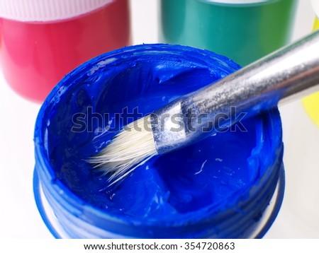 paint brush  in blue gouache jar, macro, shallow depth of field - stock photo