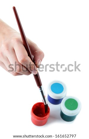 Paint brush in hand and multicolored paints isolated on white - stock photo