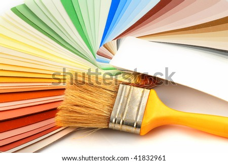 Paint brush laying on a heap of color samples - stock photo