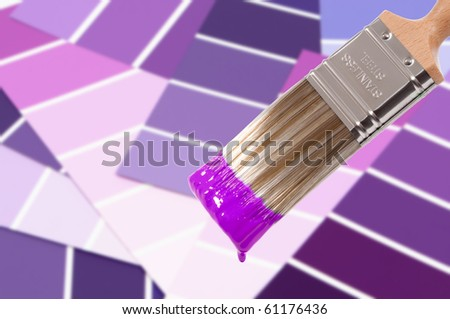 Paint brush loaded with purple paint with colour swatches below - stock photo