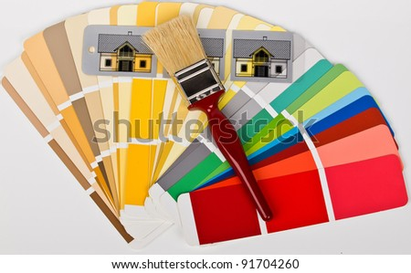 paint brush with colored houses on the swatch - stock photo