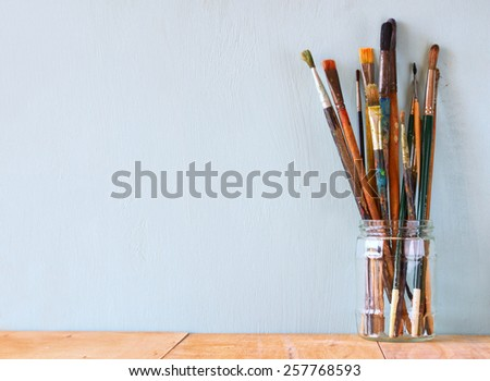 paint brushes in jar over wooden aqua blue background - stock photo
