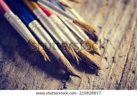 Paint brushes on rustic wooden table - stock photo