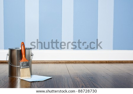 Paint can and brush against a blue striped wall - stock photo
