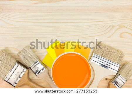 paint can and different sizes of paintbrushes with color guide on wooden background - stock photo