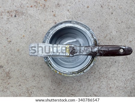 paint can on concrete with white paint and dirty paint brush - stock photo