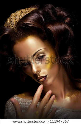 Paint. Fantasy. Glamor. Creative gold make-up, beauty woman face and fashion style - stock photo