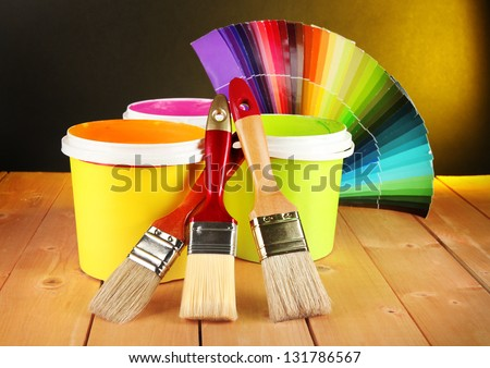 Paint pots, paintbrushes and coloured swatches on wooden table on dark yellow background - stock photo