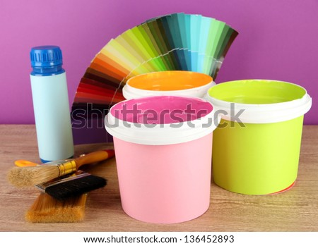 Paint pots, paintbrushes and coloured swatches on wooden table on purple background - stock photo