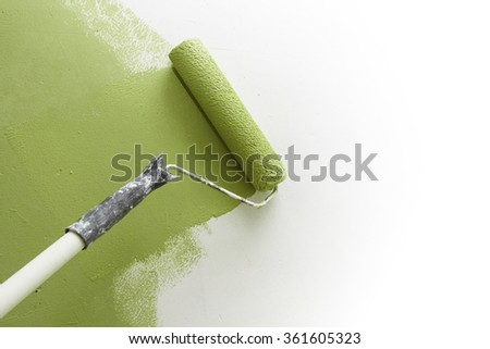 Paint roller applying green paint on white wall, home improvements, horizontal view with copy space - stock photo