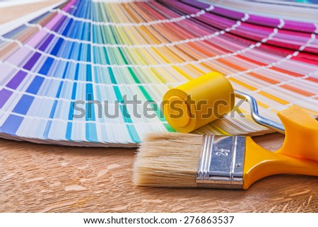 Paint roller brush and pantone color palette guide on wooden board close up view  - stock photo
