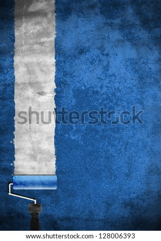 Paint roller with blue paint on white wall - stock photo